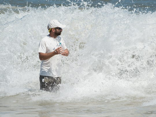 Michael Bott a environmental scientist with DNREC walks into the ocean water at Rehoboth Beach to demonstrate who he collects a water sample.