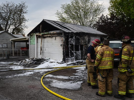 Firefighters work at the scene of a garage fire at 28 West Hanover St. on May 5, 2015.