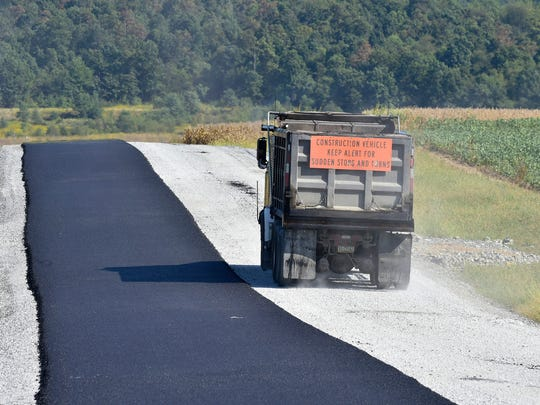 A dump truck travels along Washington Township Blvd. extended on Friday, September 23, 2016. Paving is underway from Old Forge Road to the new roundabout at North Welty Road.