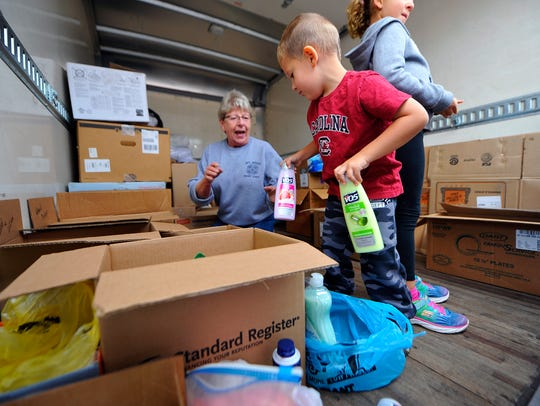Wesley Elfner, 3, of Mount Wolf, hands supplies to