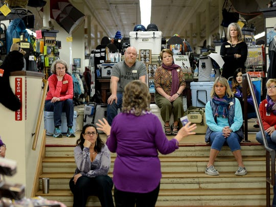 Local Pancreatic Cancer Action Network volunteer Joyce Worley, center, talks to Mast General Store employees about the disease on Wednesday, October 26, 2016. The Main Street store is showing support for the non-profit with a store-front window decorated in purple, the color that represents the cause.