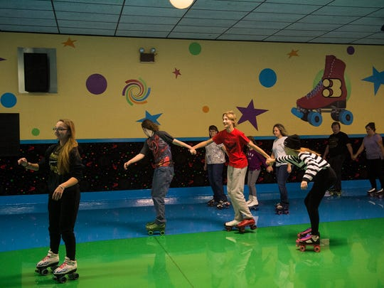 Skaters form groups per the dj's instructions during the 42nd anniversary of Magic Elm Skateland on Nov. 6, 2016.