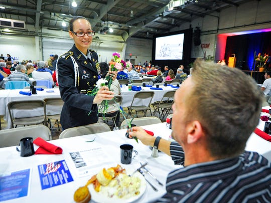 Cadet Capt. Skyee Wright hands out flowers to veterans during the annual York County Veterans Day breakfast and program at the York Expo Center, Friday, Nov. 11, 2016.  John A. Pavoncello photo