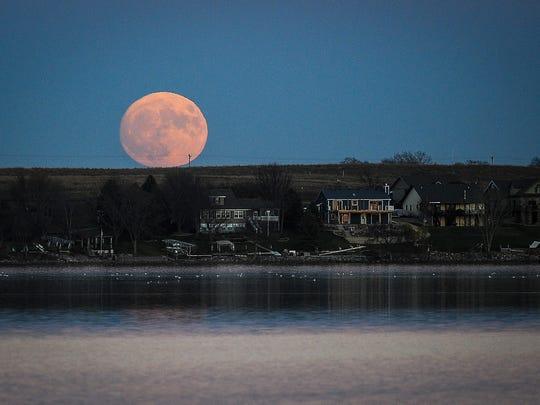 the super moon rises over Brant Lake Sunday, Nov. 13, 2016, near Chester, S.D.
