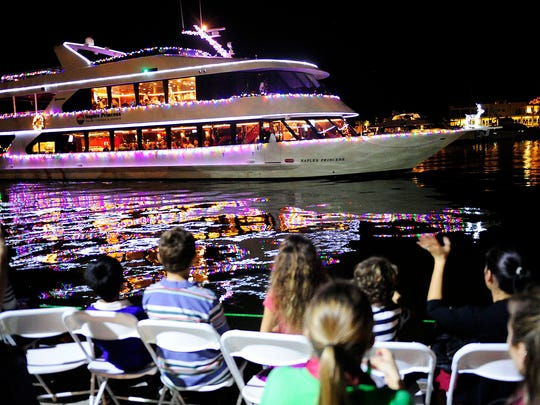 Spectators at a previous Naples Boat Parade clap and wave as the Naples Princess passes by.