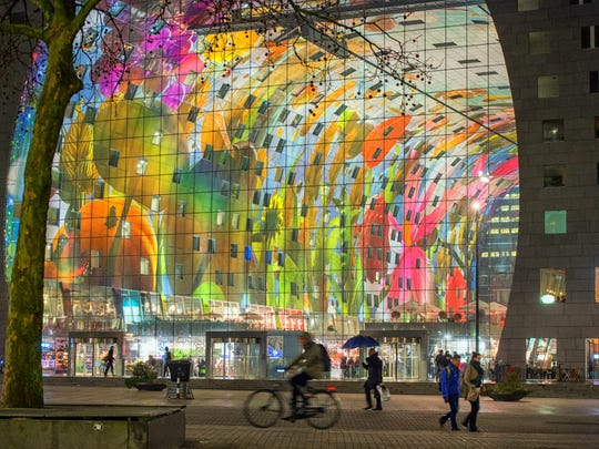 """Rotterdam is full of art and unusual architecture, including The Markthal, a residential and office building with a market hall underneath.  More than 4,000 colorful tiles cover the inside of this arch and form the largest artwork in the Netherlands: """"The Horn of Plenty,"""" by Arno Coenen and Iris Roskam."""