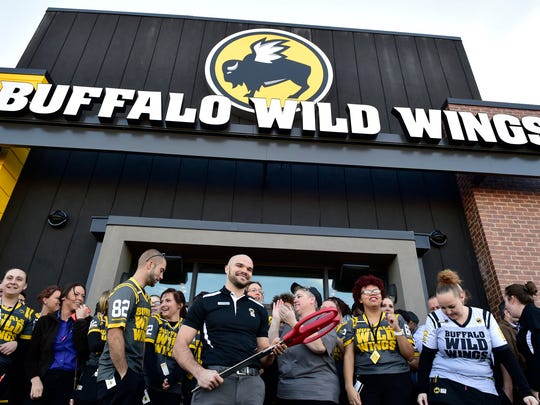 Buffalo Wild Wings opened their new location Monday, December 19, 2016 at 540 Walker Road, Chambersburg. Manager Matt Booz, center, holds the scissors after the ribbon-cutting.