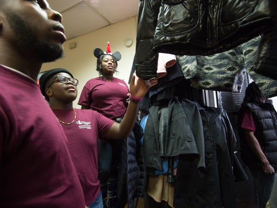 William Lee (16), left, of Wilmington, Joel Adderley (15) of New Castle and Deja Adderley of New Castle help pull coats and jackets at the 9th annual coat and jacket giveaway at Black Visionary Designers (BVD) Barber Salon in Wilmington.