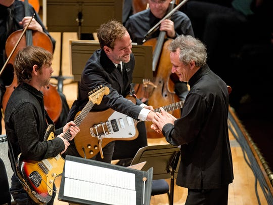 Cincinnati Symphony Orchestra conductor Louis Langrée congratulates Bryce Dessner, right, and his twin brother Aaron Dessner after a performance of Bryce's piece, St. Carolyn by the Sea in 2014.