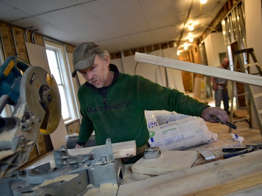 Jayson Waite, of Palmer Construction Company, cuts wood on Monday, January 23, 2017 in Public Opinion newspaper's new office space at One North Main Street, Chambersburg Memorial Square.