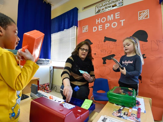 Paraprofessional Julie Poore works with students at their make believe Home Depot store front at Appoquinimink Preschool Center in Middletown.