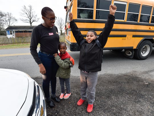 Ebony Dupont, left picks up her sons Bryson Williams (6) and Omar Vidro Pacheco Jr., (9) after getting off the school bus near their home in Seaford.