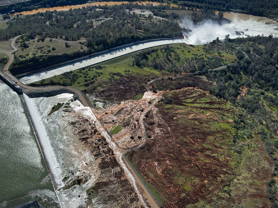 Lake water flows over the emergency spillway, bottom left, at Lake Oroville on Saturday for the first time in the nearly 50-year history of the Oroville Dam in Oroville. The dam opened in 1968.