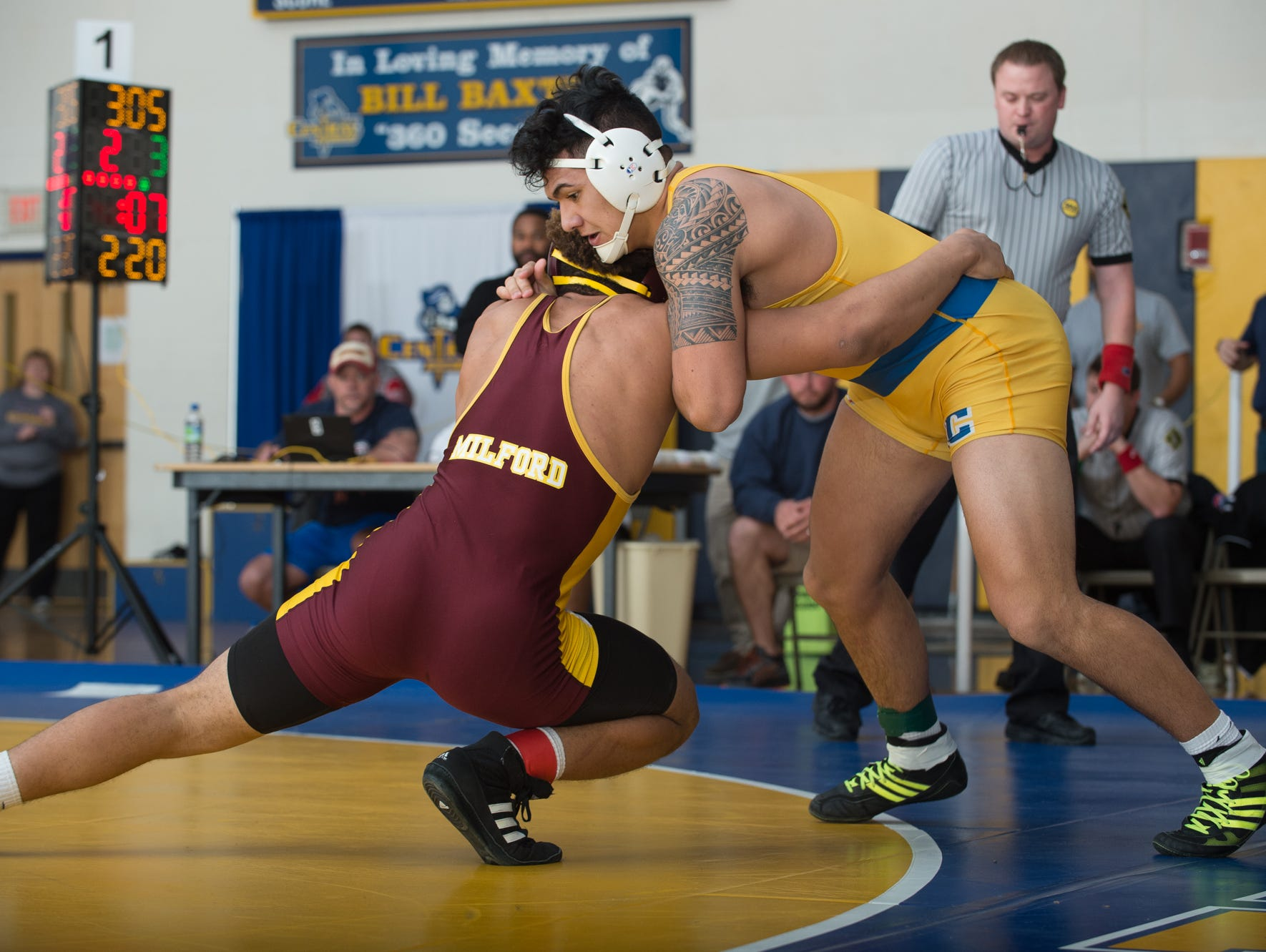 Sussex Central's Johnny Morris, right, pushes back on Milford's Dominic Covington to stay in bounce in the 220 pound championship match at the Henlopen Conference wrestling tournament at Sussex Central High School.