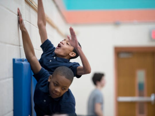 Daveyon Lynder-Rosaria, top, and Jamir Temple test their skills with a running wall jump during a parkour class at Lincoln Charter School in York
