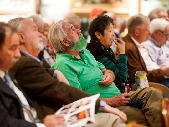 A bidder celebrates St. Patrick's day with his clothing and dyed beard while watching the screen during March in Montana at the Great Falls Elks Lodge.
