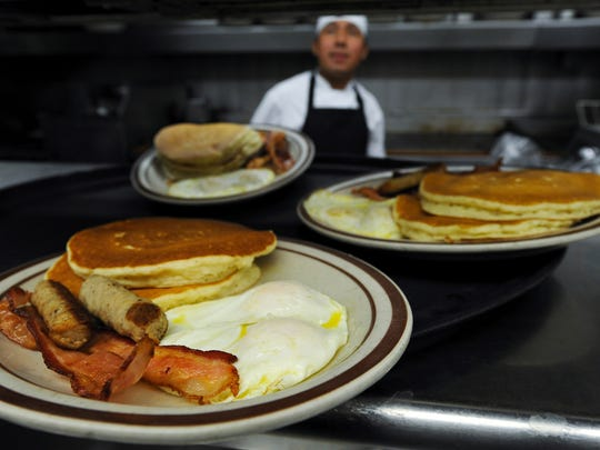 Grand slam breakfast plates await pick up by waitresses