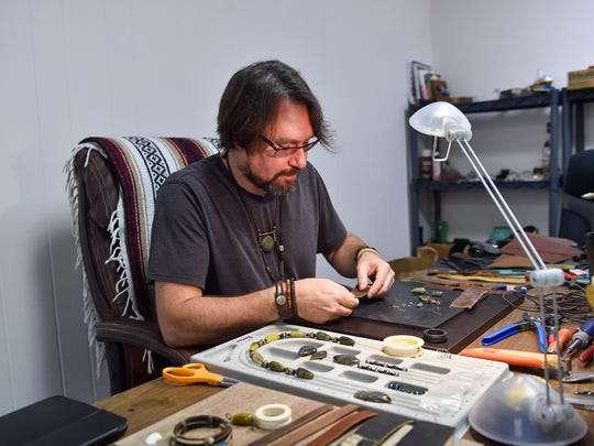 Keith Bentley carefully puts together a leather and gem bracelet at Rare Bird. The shop uses only re-purposed leather.