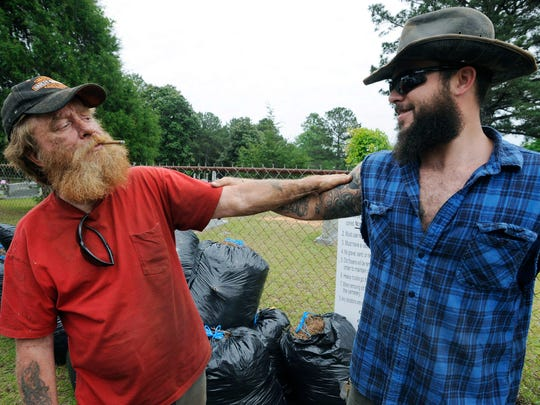 """In this Wednesday, May 3, 2017 photo,  Jimmy Frank Hicks, left, and nephew Tyler Goodson of the hit podcast """"S-Town"""" stand at the grave of friend John B. McLemore, who is also featured in the serialized show. Dimes, rocks and trinkets have started showing up on McLemore's headstone since the podcast debuted. But residents of the area depicted in the show are uneasy with their rural community being portrayed as a lousy place best described with an expletive."""