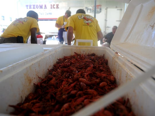 Cooked crawfish is packed into coolers as they wait
