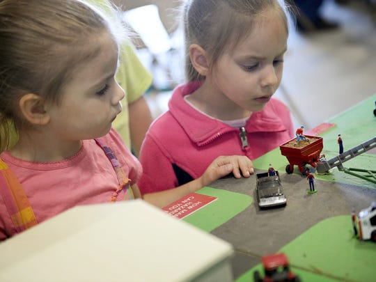 Talitha Heisey, 4, (left)  and Kymberlie Patches, 4, look for dangerous situations on a model farm as people attended the annual Farm Safety Day held at the Lebanon Valley Expo Center.