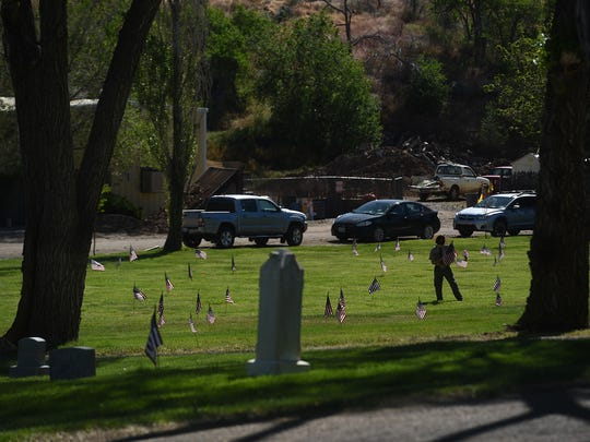 Member of Boy Scout Troop 7322 place flags on veteran's grave sites for Memorial Day at Our Mother of Sorrows Catholic Cemetery in Reno on May 27, 2017.