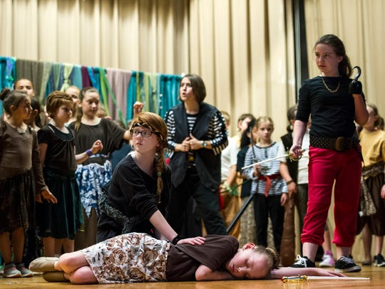 Peter Pan, played by Bethany Decamps, kneels beside