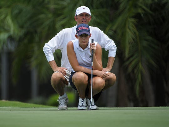 Emma Bradley of Naples looks over her putt with caddy