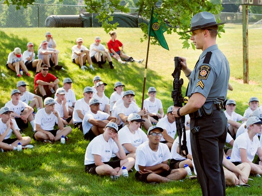 Trooper Adam Reed describes the safe way state police handle an AR-15 during a state police youth boot camp  at York College this week.