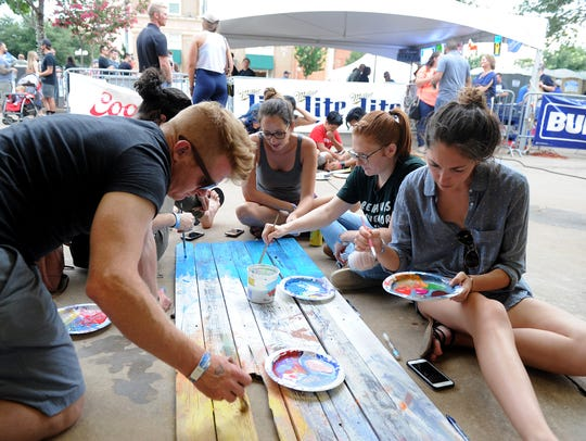 Groups paint fence posts for the Wichita Falls Alliance