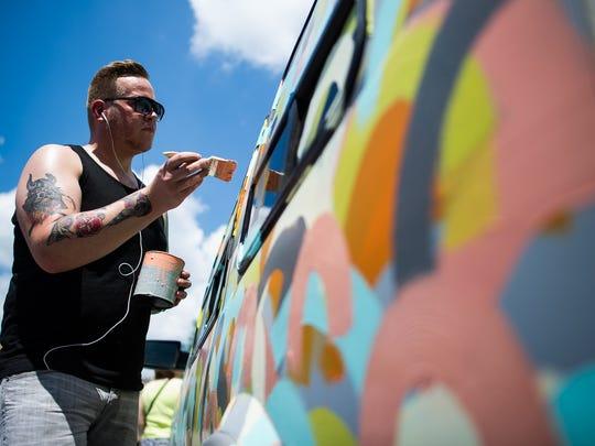 Brian Powers/The Register Artist Van Holmgren paints a van during the Des Moines Arts Festival in Western Gateway Park on Saturday. Artist Van Holmgren paints a van during the Des Moines Art Festival in Western Gateway Park on Saturday, June 27, 2015.