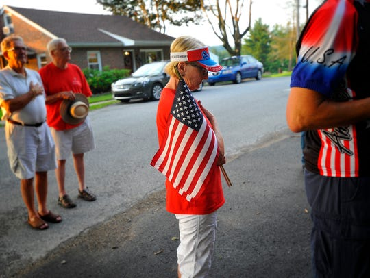 Neighbor Linda Engler holds a flag as she and others