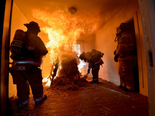 Dover Fire Department firemen start a fire for training purposes during a controlled burn of a house next to Dover High School in Dover.