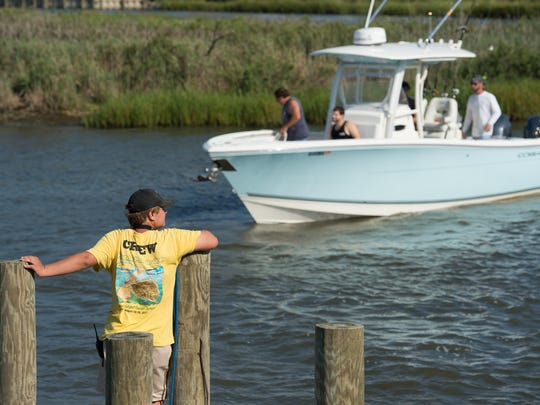 In this file photo, a crew member waits for a boat to dock during the Flounder Pounder Open at Paradise Grill in Long Neck.
