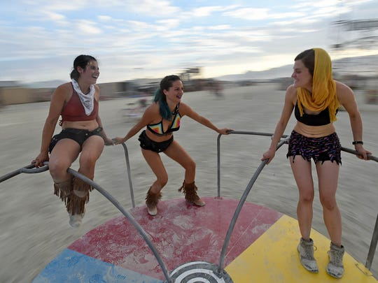 Laurel Heller, left, Krista Lockwood and Courtney Ives have fun on a marry-go-round at Burning Man on the Nevada Black Rock Desert on August 27, 2017.