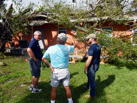 Martin Zickert (from left), Victor Diaz and Doy Demsick survey damage done to a residence for homeless veterans Monday, Sept. 11, 2017, in Vero Beach. The damage was caused by a large tree that had fallen onto the structure as Hurricane Irma made its way across the Treasure Coast.