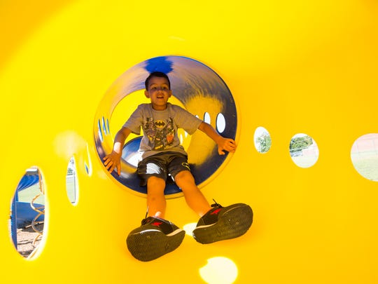 Kamerin Truitt, a first-grade student at Georgetown Elementary School, plays in the tunnel at the district's new adaptive playground. The new playground equipment can accommodate all students, including those with disabilities.