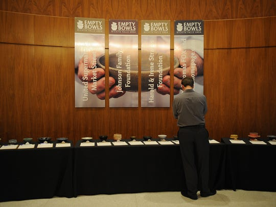 A man browses the silent auction at the Empty Bowls