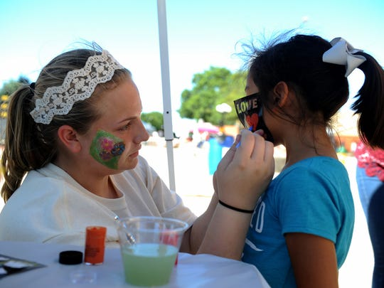 Micah Scobee paints a heart on Gracelyn Barboza's cheek at the 8th Annual Calle Ocho Saturday, Oct. 7, 2017, at the Wichita Falls Farmers Market.