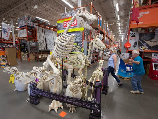 People run past a giant dinosaur skeleton at the Home