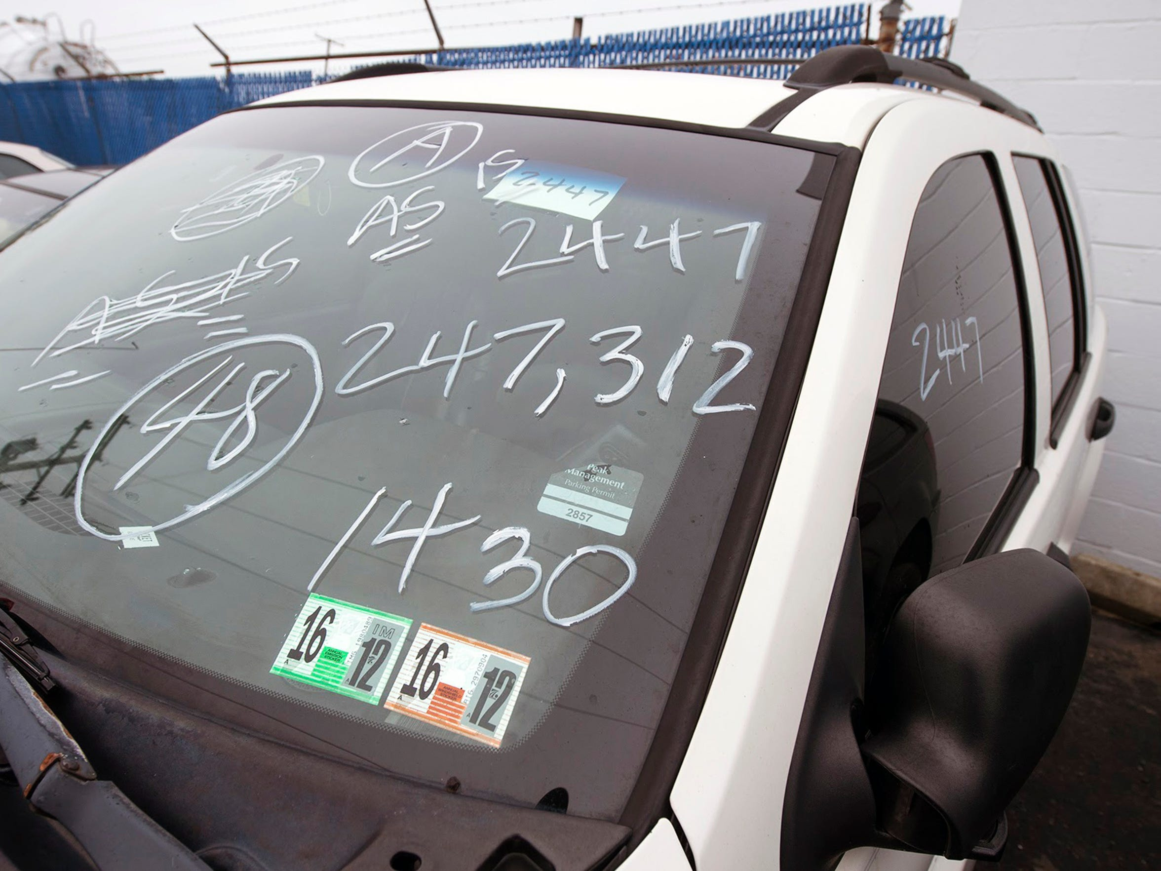 Details about a vehicle, written on the windshield, show that it has 247,312 miles on the odometer during the York County Drug Task Force auction in May of 2017.