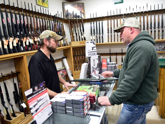 Store mananger Jeromy Dinsmore, left, helps customer