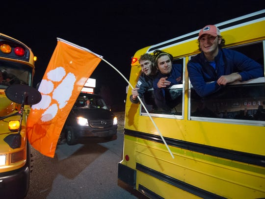 Delmar's Hunter Gilmore, left, Nicholas Davis and Patrick Spence celebrate with fans after returning home from their 14-7 victory over Milford in the DIAA Division II championship game Saturday night at Delaware Stadium.