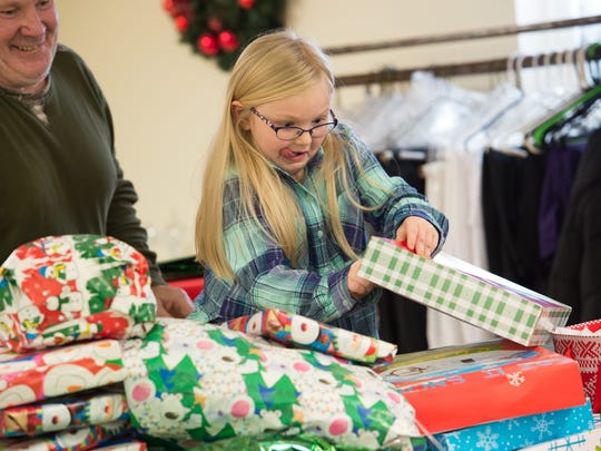 Mackaliegh Slaughter, 6, opens Christmas gifts during a luncheon at Centennial Church in Smyrna.