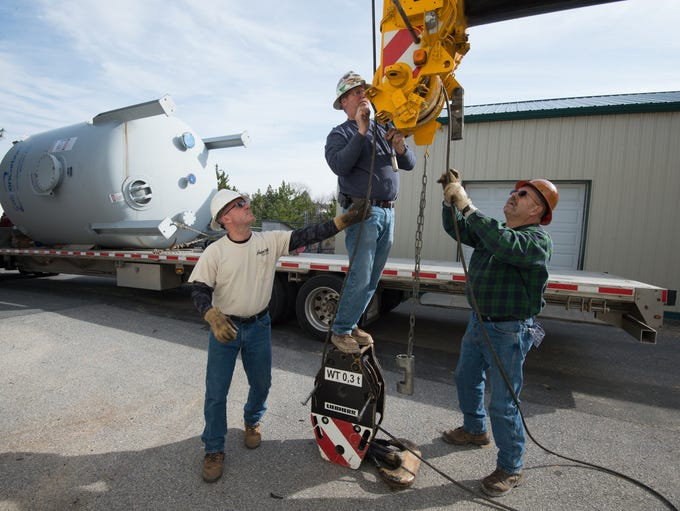 Workers with Aerial Crane prepare to unload a carbon