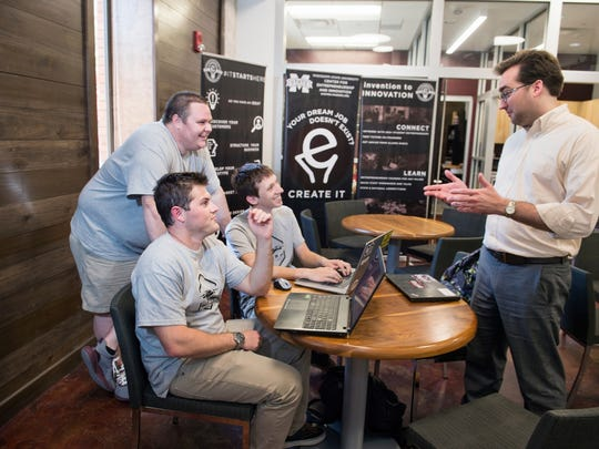 Conor Ferguson, standing left, along with Joseph Cuty and Logan Smith, seated from left, talk with MSU Center for Entrepreneurship and Outreach Director Eric Hill in McCool Hall. Along with a team of entrepreneurship advisory board members and other mentors from the Bulldog family, Hill has helped the WISPr Systems business team successfully navigate the start-up process.