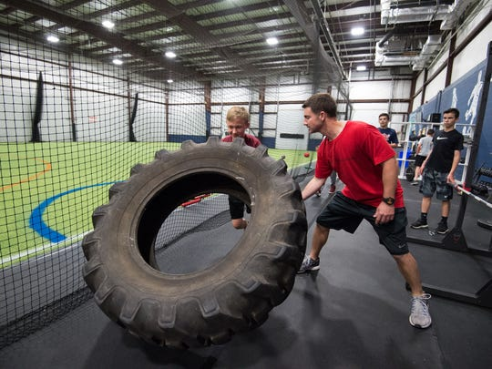 Jeff Simpson, right, owner and head strength coach with Sports Specific Training, helps Carter Boyd (12) flip over a tire during a training session at Slim's Sport Complex in Middletown.