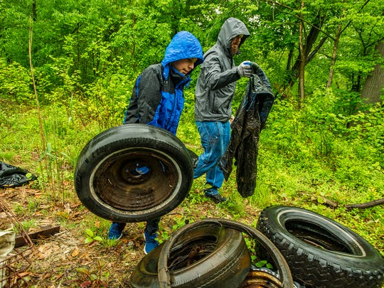 (L-R) Chris Cioffi, 12, of Morristown and Environmental Commission Commissioner Nathan Umbriac of Morristown pick up some trash by Pocahontas Lake at the cleanup of Speedwell and Pocahontas Lake in Morristown, May 19, 2018.  Photo by Warren Westura for the Daily Record.