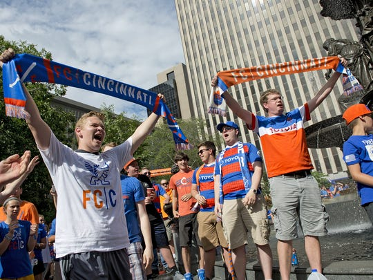 Thousands of FC Cincinnati Soccer fans gathered on Fountain Square on Tuesday, May 29, 2018 to watch a live broadcast from Rhinegeist Brewery announcing that the team was accepted into Major League Soccer. Eli Hughes of Loveland and Steve Doran of Walnut Hills hold their FC scarfs high as the rouse the crowd with a soccer chant.