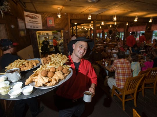 A Cock-of-the-Walk server heads to a table with a tray full of Mississippi fried catfish, hushpuppies and fries at the Ridgeland restaurant.